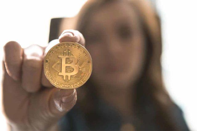 Une personne montrant un bitcoin
